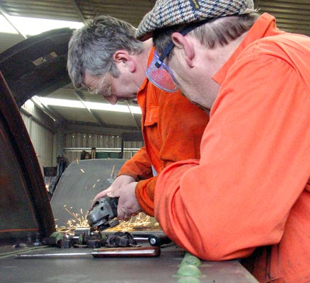 Keith Lines grinds a rivet head off on the running plate as John Salter watches. February 21 2004