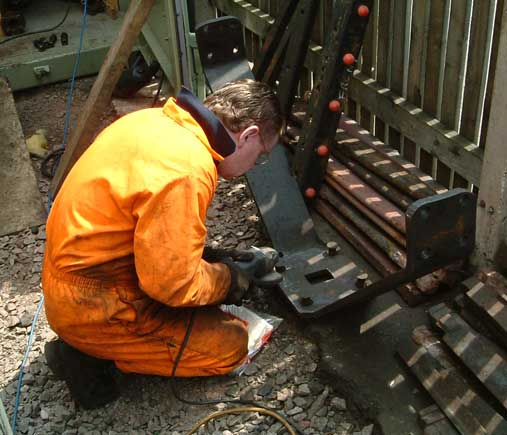 Kevin Blake cleans up the wishbone before it was refitted. This item sits behind the front buffer beam between the frames and in front on the centre cylinders. May 31 2003 © Colin Henderson