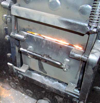 The firehole door on Owl, when seen in April 2004, was of a new design on test. The door opens vertically and is held open by a spring. When in the running position, as seen here, the door is held open by moveable metal catches. These can be removed to fully close the door but are designed to be awkward to adjust on the move to encourage GPCS operation ! On the fire side of the door is a air duct system as on Owl and Badger. However in this case all secondary air is admitted around the edge of the door with much being sucked behind the air ducting system. April 11 2004
