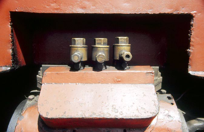 "This cover covers the site of the drifting valves removed during the modification. The 3 prominent brass fittings are high pressure terminal check valves on the mechanical lubrication feed providing ""between the rings"" lubrication of the piston valves, 1 for each head, and a feed to the piston. 1998. © Nigel A.H.Day"