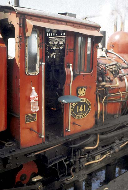 A rear view of 141's cab on the drivers side. Note the bottle of water and the movable seat both outside of the cab to help the water and the driver stay cool in the very hot operating conditions. The curve in the cabside is the accomodate the screw reverser handle. 1998. © Nigel A.H. Day.